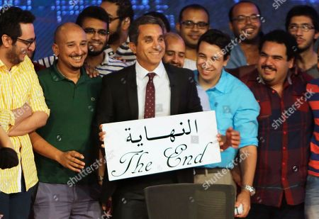 "Bassem Youssef Egyptian satirist Bassem Youssef, who is known as ""Egypt's Jon Stewart,"" poses with his team with an English and Arabic placard reading ""the end,"" during a press conference in Cairo, Egypt, . Youssef said Monday he has canceled his landmark TV show, which broke ground by lambasting its politicians and elites and mocking the pro-military fervor of the past year. Youssef said the atmosphere in the country no longer allows for political satire"