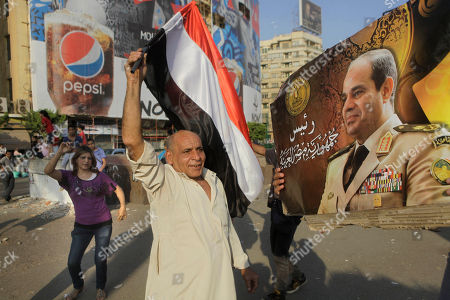 """Supporters of Egypt's president-elect Abdel-Fattah el-Sissi dance around his poser as they celebrate Tuesday's official announcement declaring him the next president at Tahrir Square in Cairo, Egypt, . Arabic reads, """"The President of the Arab Republic of Egypt."""" Interim President Adly Mansour will hand over office to former army chief el-Sissi, who oversaw Islamist President Mohammed Morsi's removal and who won last week's presidential elections in a landslide. El-Sissi is to be sworn in on Sunday"""