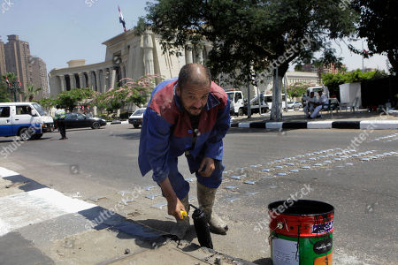 An Egyptian worker paints the curb of the pavement in front of the supreme constitutional court in Cairo, Egypt, where elected president Abdel-Fattah el-Sissi will be sworn in, on Sunday. Interim President Adly Mansour will hand over office to former army chief el-Sissi, who oversaw Islamist President Mohammed Morsi's removal and who won last week's presidential elections in a landslide