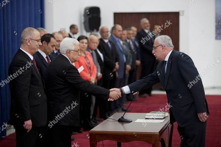 Stock Image of Riyad al-Malik, Mahmoud Abbas, Rami Hamdallah Palestinian Foreign Minister Riyad al-Malik, right, shakes hands with President Mahmoud Abbas as Prime Minister Rami Hamdallah, left, watches during a swearing-in ceremony of its unity government in the West Bank city of Ramallah on . Ramallah on Monday, June 2, 2014. Abbas on Monday swore in a Palestinian unity government, taking a major step toward ending a crippling territorial and political split among the Palestinians but also setting the stage for new friction with Israel