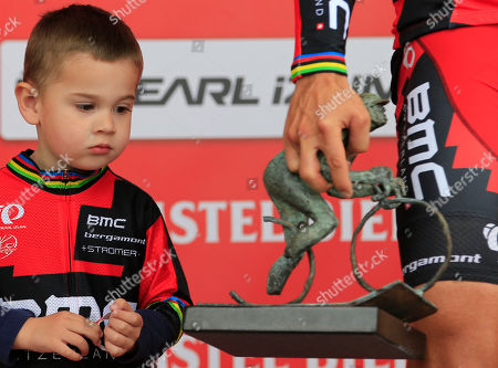 Three-and-a-half-year-old Alan Gilbert watches the trophy as his father Philippe walks off the podium with the trophy after winning the 49th edition of the Amstel Gold Cycling Race over 251.8 kilometers (156.5 miles) with start in Maastricht and finish in Valkenburg, southern Netherlands