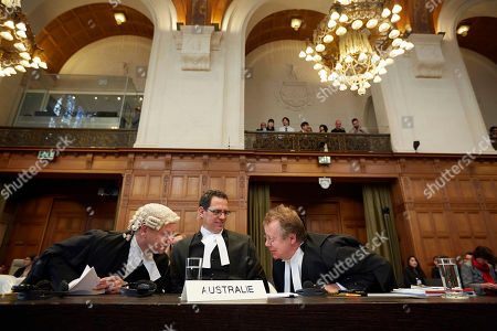 Australian Professor of Law, Philippe Sands, left, Justin Gleeson, center, and Bill Campbell, right, wait for the International Court of Justice to deliver its verdict in The Hague, Netherlands, . The International Court of Justice is ruling Monday on Australia's challenge against Japan for whaling in Antarctic waters