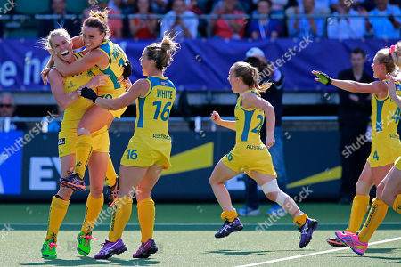 Australia's Georgie Parker and Australia's Kellie White, second and third left, hug Jodie Kenny, far left, who scored the decisive goal in the shootout during the Field Hockey World Cup semifinal match women between the U.S. and Australia in The Hague, Netherlands, . The match ended in a 2-2 draw, Australia won the shootout 3-1 and continues to the final