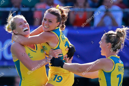 Australia's Georgie Parker, center, and Australia's Kellie White, right, hug Jodie Kenny, left, who scored the decisive goal in the shootout during the Field Hockey World Cup semifinal match women between the U.S. and Australia in The Hague, Netherlands, . The match ended in a 2-2 draw, Australia won the shootout 3-1 and continues to the final