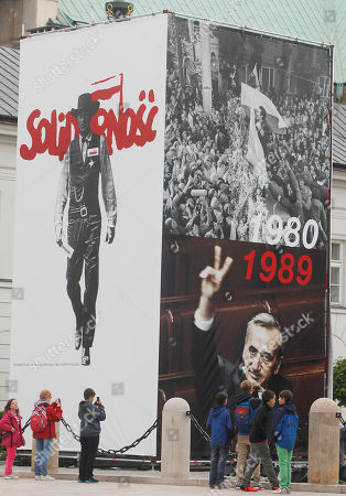 Pictures of Lech Walesa leading the 1980 strike that gave rise to the Solidarity freedom movement, top right, and of prime minister Tadeusz Mazowiecki flashing a v-sign in 1989, bottom right, are on display in front of the Presidential Palace in Warsaw, Poland, on the eve of the visit of US President Barack Obama and other European leaders who will attend celebrations marking 25 years of Poland's democracy