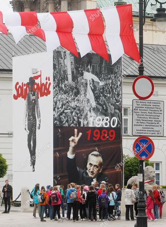 Poland's national white-and-red flags, and pictures of Lech Walesa leading the 1980 strike that gave rise to the Solidarity freedom movement, top, and of prime minister Tadeusz Mazowiecki flashing a v-sign in 1989 are on display in front of the Presidential Palace in Warsaw, Poland, on the eve of the visit of US President Barack Obama and other European leaders who will attend celebrations marking 25 years of Poland's democracy