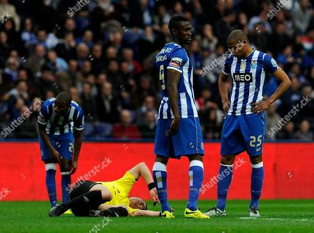 Portuguese referee Manuel Mota grimaces in pain after being hit by the ball, with FC Porto's Ricardo Pereira, Jackson Martinez and Fernando Reges, from left to right, in a Portuguese League soccer match between FC Porto and Academica at the Dragao stadium in Porto, Portugal, . Referee Mota was substituted at half time