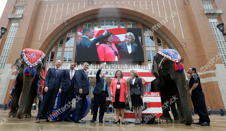 Reince Priebus, Phillip Jones, Ray Washburne, Mike Rawlings, Enid Mickelsen, Kay Bailey Hutchison Posing with live elephants, Republican National Committee chairman Reince Priebus, center right, waves with, from left, Phillip Jones, Ray Washburne, Dallas Mayor Mike Rawlings, Enid Mickelsen and former U.S. Sen. Kay Bailey Hutchison in front of the American Airlines Center during a visit by members of the Republican National Committee scouting a 2016 Convention host site in Dallas, . American Airlines Center would serve as the convention site if Dallas' bid is successful. Dallas is competing with Denver, Cleveland and Kansas City