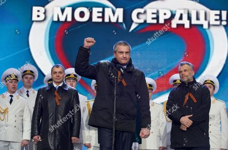 "Sergei Aksyonov, Alexei Chalyi, Vladimir Konstantinov Crimean leaders, from left, Speaker of Crimean legislature Vladimir Konstantinov, Crimean Premier Sergei Aksyonov and Sevastopol mayor Alexei Chalyi, wearing ribbons symbolizing the Soviet victory in WWII, attend a rally in support of Crimea joining Russia in Red Square in Moscow, . With a sweep of his pen, President Vladimir Putin added Crimea to the map of Russia on Tuesday, describing the move as correcting past injustice and responding to what he called Western encroachment upon Russia's vital interests. The sign in the back says ""Crimea is in my heart"