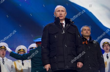 Vladimir Putin, Sergei Aksyonov Russian President Vladimir Putin sings national anthem at a rally in support of Crimea joining Russia in Red Square in Moscow, . With a sweep of his pen, President Vladimir Putin added Crimea to the map of Russia on Tuesday, describing the move as correcting past injustice and responding to what he called Western encroachment upon Russia's vital interests. At right is Crimean Premier Sergei Aksyonov