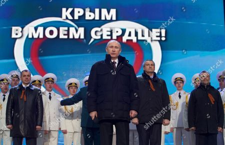 "Vladimir Putin, Sergei Aksyonov, Alexei Chalyi, Vladimir Konstantinov Russian President Vladimir Putin, with Crimean leaders in the background, sings the national anthem at a rally in support of Crimea joining Russia in Red Square in Moscow, . With a sweep of his pen, President Vladimir Putin added Crimea to the map of Russia on Tuesday, describing the move as correcting past injustice and responding to what he called Western encroachment upon Russia's vital interests. In the background from left, Speaker of Crimean legislature Vladimir Konstantinov, Crimean Premier Sergei Aksyonov and Sevastopol mayor Alexei Chalyi. The sign in the back says ""Crimea is in my heart"