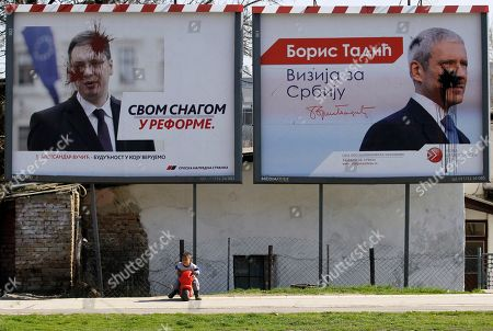 "A child rides a toy bike in front of smeared placards featuring populist leader Aleksandar Vucic with a slogan reading: ""Strongly for reforms"", left and former president Boris Tadic with slogan: ""Vision for Serbia"" reflecting widespread disappointment with politicians in the impoverished Balkan country, in Belgrade, Serbia, . Serbian parliamentary elections are scheduled for Sunday, March 16"