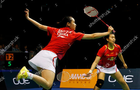 Stock Image of Bao Yixin, Tang Jinhua Bao Yixin, left, and Tang Jinhua, right, of China return a shot to Kamilla Rytter Juhl, and Christinna Pedersen of Denmark during their women's doubles final match at the Singapore Open Badminton championship on in Singapore