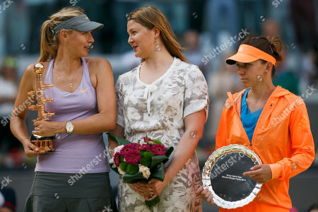 Stock Photo of Maria Sharapova, Simona Halep, Dinara Safina Maria Sharapova from Russia, left, celebrates her victory holding her trophy as she talks to former tennis player Dinara Safina, center, and Simona Halep from Romania, right, after a Madrid Open tennis tournament final match in Madrid, Spain