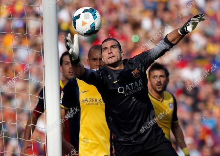 Barcelona goalkeeper Jose Manuel Pinto jumps for the ball during a Spanish La Liga soccer match between FC Barcelona and Atletico Madrid at the Camp Nou stadium in Barcelona, Spain