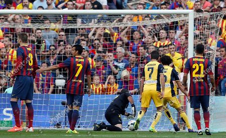 Barcelona goalkeeper Jose Manuel Pinto, center, looks for the ball after receiving a goal during a Spanish La Liga soccer match between FC Barcelona and Atletico Madrid at the Camp Nou stadium in Barcelona, Spain