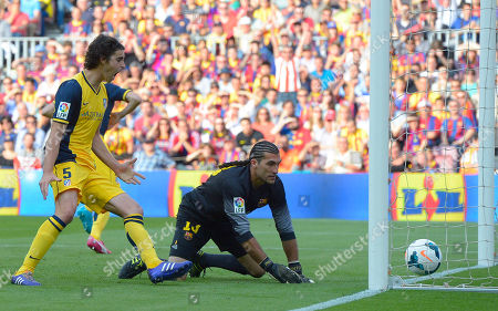 Atletico's Tiago Mendes, left, celebrates the goal of Atletico's Diego Godin, from Uruguay, as Barcelona goalkeeper Jose Manuel Pinto looks on during a Spanish La Liga soccer match between FC Barcelona and Atletico Madrid at the Camp Nou stadium in Barcelona, Spain