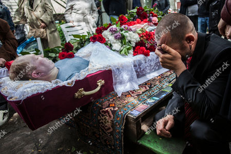 A man cries while mourning at the body of Alexey Vorobyov, a civilian killed by Ukraine National Guard during an operation against pro Russian activist last Friday in Mariupol, during the funeral in Mariupol, Ukraine, . Pro-Russia insurgents in eastern Ukraine declared independence Monday, a day after holding a hastily arranged referendum vote on separatism that Ukraine's government and its western allies said violated international law