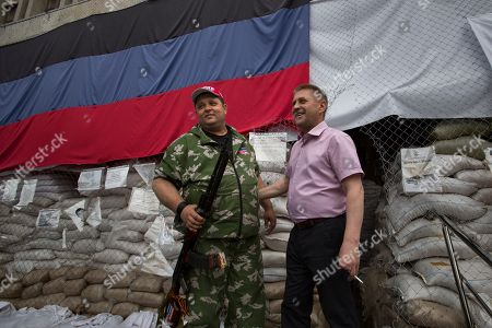 Stock Image of Vyacheslav Ponomarev Vyacheslav Ponomarev, right, the self-proclaimed mayor of Slovyansk speaks to journalists in front of an administrative building seized by pro-Russian militants in Slovyansk, Ukraine, with a huge Donetsk People's Republic flag in the background. Rebels in eastern Ukraine shot down a government military helicopter Thursday amid heavy fighting around the eastern city of Slovyansk, killing 14 soldiers including a general, Ukraine's leader said. Acting President Oleksandr Turchynov told the parliament in Kiev that rebels used a portable air defense missile Thursday to down the helicopter and said a General was among the dead