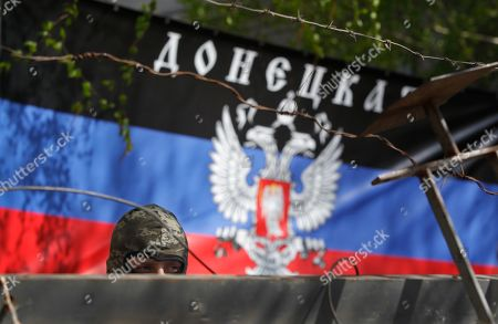 "A pro-Russian protester guards barricades with a banner reading ""Donetsk Republic"" in Slovyansk, eastern Ukraine, . Vyacheslav Ponomaryov the self-proclaimed mayor of Slovyansk in eastern Ukraine is appealing to Russia to send in peacekeeping troops after a shootout at checkpoint near the city manned by pro-Russia insurgents"