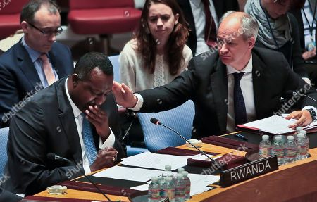 Britain's Deputy Ambassador Peter Wilson, right, reaches to comfort Rwanda's U.N. Ambassador Eugene Gasana, left, who becomes emotional while addressing the U.N. Security Council on . Gasana broke down as he expressed support for a new U.N. medal for peacekeepers who have demonstrated acts of bravery, named for Senegalese peacekeeper Captain Mbaye Diagne. Gasana recalled Diagne's bravery saving hundreds of Rwandans during the genocide of 1994