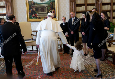 Pope Francis holds by her hand Giorgia May, granddaughter of Malta's President George Abela, left, during a private audience in the Pontiff's studio at the Vatican