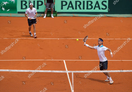 Stock Picture of Fabio Fognini, Simone Bolelli Italy's Fabio Fognini, front, returns the ball to Argentina's Horacio Zeballos and Eduardo Schwank, as his teammate Simone Bolelli looks on during their Davis Cup doubles match in Mar del Plata, Argentina