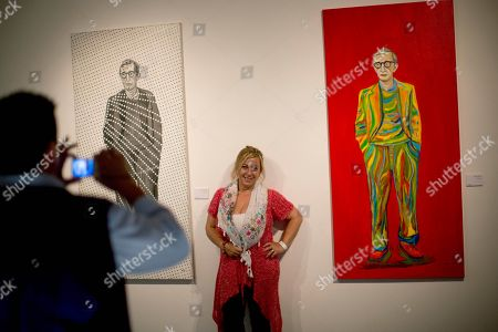 "A woman poses for a photography between paintings of U.S. director Woody Allen at an art exhibit titled ""Queremos tanto a Woody,"" or ""We so love Woody"" by Argentine artist Hugo Echarri in Buenos Aires, Argentina, . The exhibit in honor of Allen was inaugurated just days after the artist faced renewed accusations that he molested Dylan Farrow, his then-7-year-old adopted daughter in 1992"