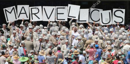 Fans, dressed like former cricket commentator Richie Benaud, hold up a sign after an England wicket fell during their Ashes cricket test match against Australia in Sydney, Australia
