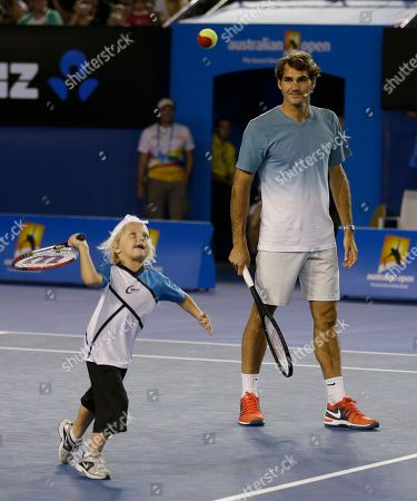 Switzerland's Roger Federer watches as Cruz Hewitt, son of Australian player Lleyton, attempts to hit a ball during an exhibition match on Kids Tennis Day ahead of the Australian Open tennis championship in Melbourne, Australia, Saturday, Jan.11, 2014