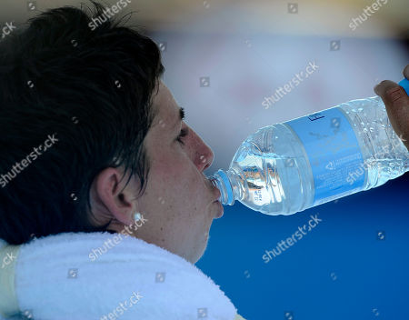 Carla Suarez Navarro of Spain takes a drink with ice towel around her neck between games during her second round match against Galina Voskoboeva of Kazakhstan at the Australian Open tennis championship in Melbourne, Australia