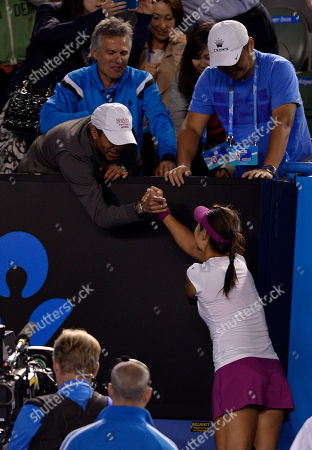 Li Na of China celebrates with her husband Jiang Shan, right, and support team members after defeating Dominika Cibulkova of Slovakia in their women's singles final at the Australian Open tennis championship in Melbourne, Australia