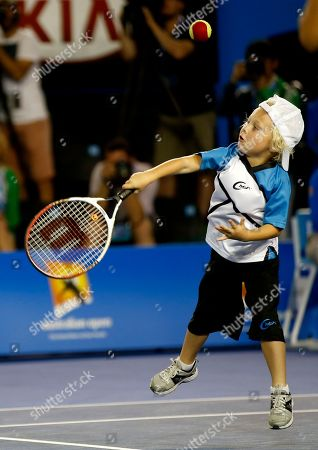 Cruz Hewitt, son of Australian player Lleyton, attempts to hit a ball during an exhibition match on Kids Tennis Day ahead of the Australian Open tennis championship in Melbourne, Australia, Saturday, Jan.11, 2014