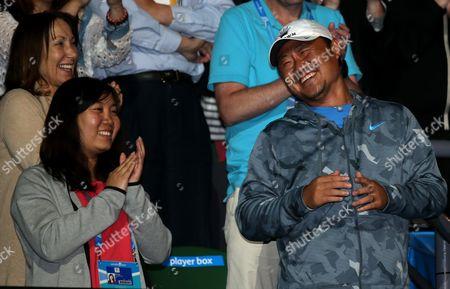 Husband of China's Li Na, Jiang Shan, right, celebrates with Li's support team members after Li won over Dominika Cibulkova of Slovakia in their women's singles final at the Australian Open tennis championship in Melbourne, Australia