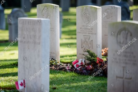 The headstone of British World War One soldier Lt. Maurice Dease, center, is positioned between other headstones at St. Symphorien Military Cemetery near Mons, Belgium. Dease was awarded one of the first British Victoria Crosses of the war, for defending the canal crossings in Mons during one of the first battles of the war