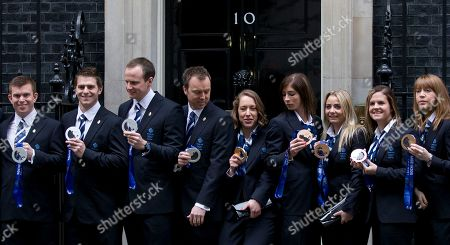Britain's Olympic 2014 winter games gold medal winner Lizzie Yarnold, centre, smiles as she poses for the media by the doorstep of 10 Downing Street in London, Yarnold won gold in the women's skeleton competition. She is standing between members of the men's and women's curling teams who won sliver and bronze medals at the games