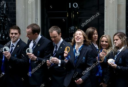 Stock Picture of Britain's Olympic 2014 winter games gold medal winner Lizzie Yarnold, centre, smiles as she poses for the media by the doorstep of 10 Downing Street in London, Yarnold won gold in the women's skeleton competition. She is standing between members of the men's and women's curling teams who won sliver and bronze medals at the games