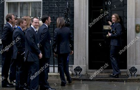 Stock Picture of Britain's Olympic 2014 winter games gold medal winner Lizzie Yarnold smiles as she knocks on the door of 10 Downing Street in London, Yarnold won gold in the women's skeleton competition