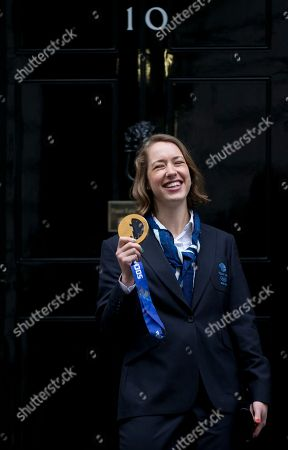 Stock Photo of Britain's Olympic 2014 winter games gold medal winner Lizzie Yarnold smiles as she poses for the media by the doorstep of 10 Downing Street in London, Yarnold won gold in the women's skeleton competition