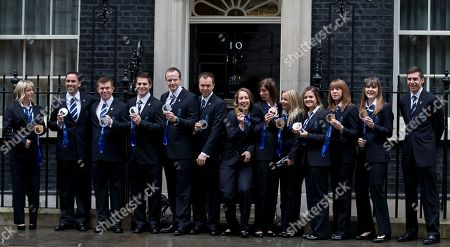 Stock Image of Britain's Olympic 2014 winter games medal winners pose by the doorstep of 10 Downing Street in London, including gold medal winner Lizzie Yarnold, centre, who the women's skeleton competition at the games