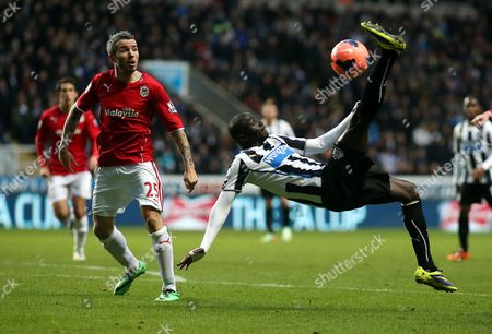 Newcastle United's Papiss Cisse, right, has a shot towards goal past Cardiff City's Kevin McNaughton, left, during their English FA Cup third round soccer match at St James' Park, Newcastle, England