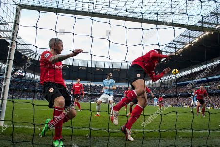 Manchester City's Edin Dzeko, second right, scores against Cardiff City despite a desperate attempt to clear the ball by Kevin McNaughton, left, during their English Premier League soccer match at the Etihad Stadium, Manchester, England