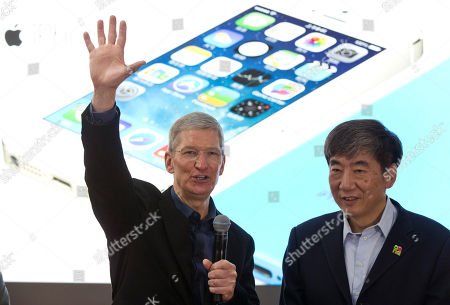 Tim Cook, Xi Guohua Apple's CEO Tim Cook, left, gestures as China Mobile's chairman Xi Guohua looks on during a promotional event that marks the opening day of sales of China Mobile's 4G iPhone 5s and iPhone 5c at a shop of the world's largest mobile phone operator in Beijing, China
