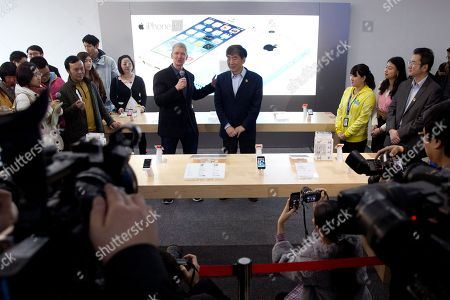 Tim Cook, Xi Guohua Apple CEO Tim Cook, center left, speaks with China Mobile Chairman Xi Guohua, center right, during a promotional event that marks the opening day of sales of China Mobile's 4G iPhone 5s and iPhone 5c at a shop of the world's largest mobile phone operator in Beijing, China