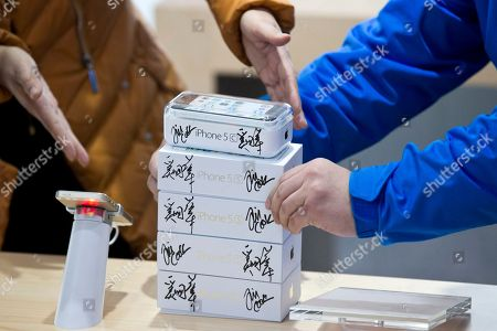Stock Photo of Shop keepers arrange boxes of China Mobile's 4G iPhone 5s and iPhone 5c with signatures of Apple CEO Tim Cook and China Mobile Chairman Xi Guohua before a promotional event that marks the opening day of sales of China Mobile's 4G iPhone 5s and iPhone 5c at a shop of the world's largest mobile phone operator in Beijing, China