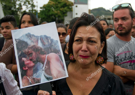 CORRECTS TO EX-HUSBAND - A woman holds up a picture of slain former Miss Venezuela Monica Spear and her ex-husband Henry Thomas Berry during a protest against violence in Caracas, Venezuela, . Venezuelan authorities say that Spear and her ex-husband were shot and killed resisting a robbery after their car broke down late Monday, Jan. 6, 2014 near Puerto Cabello, Venezuela's main port