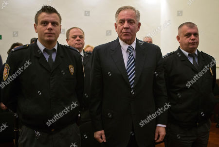 Former Croatia's prime minister Ivo Sanader, center, stands between guards in the courtroom in Zagreb, Croatia, . A court in Croatia has convicted the once powerful prime minister of siphoning millions in state money while in power, and sentenced him to nine years in prison as part of efforts by EU's newest member to root out corruption