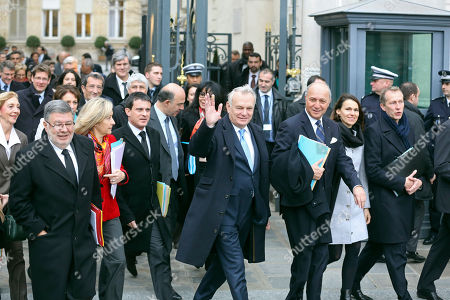 French prime minister Jean Marc Ayrault, center, waves to reporters as he walks with government members toward the Elysee Palace to attend the first cabinet meeting of the year, in Paris, . Ayrault and his ministers were gathered at the Interior ministry for the traditional New Year breakfast. Walking at his right is interior minister Manuel Vals, and at his left foreign minister Laurent Fabius