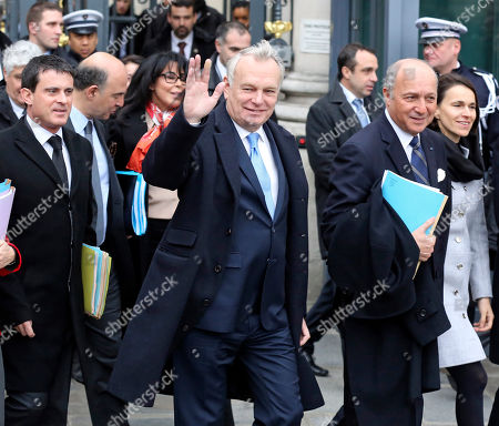 French prime minister Jean Marc Ayrault, center, waves to reporters as he walks with government members toward the Elysee Palace to attend the first cabinet meeting of the year, in Paris, . Ayrault and his ministers were gathered at the Interior ministry for the traditional New Year breakfast. Walking at left is interior minister Manuel Vals, and at right foreign minister Laurent Fabius
