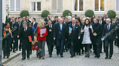 French Prime Minister Jean Marc Ayrault, center, with at his left foreign minister Laurent Fabius, and at his right interior minister Manuel Vals, walk with government members toward the Elysee Palace to attend the first cabinet meeting of the year, in Paris, . Ayrault and his ministers were gathered at the Interior ministry for the traditional New Year breakfast